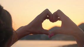 Die Hände, die ein Herz bilden, formen mit Sonnenuntergangschattenbild Die Ozeansonne, die durch Herz scheint, formte weibliche H stock footage