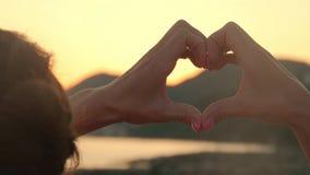 Die Hände, die ein Herz bilden, formen mit Sonnenuntergangschattenbild Die Ozeansonne, die durch Herz scheint, formte weibliche H stock video footage