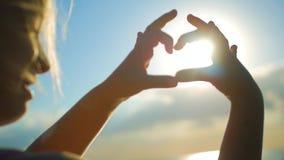 Die Hände, die ein Herz bilden, formen mit Sonnenuntergangschattenbild Die Ozeansonne, die durch Herz scheint, formte weibliche H stock video