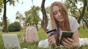Die Hände einer Nahaufnahme des jungen Mädchens, liegend auf Natur, schließt Käufe über das Internet mit einer Kreditkarte unter  stock video