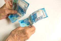 Die Hände eines alten Pensionärs betrachten Geld von einem großen Die Hände eines Mannes sind alt, altersschwach lizenzfreies stockbild
