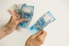 Die Hände eines alten Pensionärs halten Geld von einem großen Die Hände eines Mannes sind alt, altersschwach stockbilder