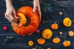 Die Hände, die Halloween-Kürbis feiern öffnen an, horizontale Ansicht des Holztischs Süßes sonst gibt's Saures von oben Stockfotografie