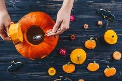 Die Hände, die Halloween-Kürbis feiern öffnen an, horizontale Ansicht des Holztischs Süßes sonst gibt's Saures von oben Lizenzfreies Stockbild
