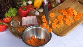 Die Hände, die Karotten drehen, schnitten in ein hölzernes Brett, gegen den Hintergrund des Huhns, Rindfleisch, Kap, Gemüse Noch  stock video