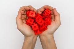 Die Hände, die roten Plastik halten, blockiert die Schaffung von Herzen Form lokalisiertes O Lizenzfreie Stockbilder