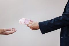 Die Hände und das Geld des Mannes in seinen Palmen Lizenzfreie Stockbilder