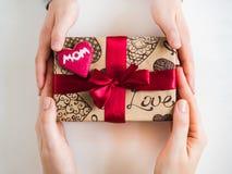 Die Hände und ein Kasten der Kinder mit einem Geschenk lizenzfreies stockbild