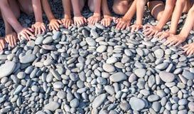 Die Hände vieler Kinder bilden ein Halbrund auf dem Strand Lizenzfreie Stockbilder