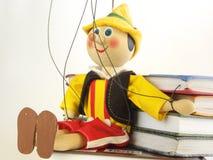 Die hölzerne Marionette und die Bücher Stockfoto