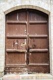 Die hölzerne Tür auf den alten Wänden Lizenzfreies Stockfoto