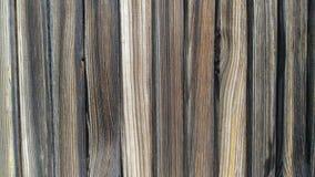Die hölzernen Bretter, die vertikal gelegen sind, masern das alte, gedrehte schwarze Holz Stockbilder
