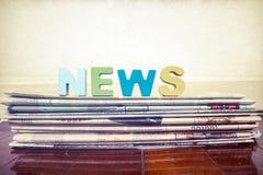 Die hölzernen Buchstaben des Wortnachrichten-Schenkels auf alter Zeitung Stockfotos