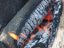 Die hölzernen Klotz brennen im Feuer, bevor sie ein Lebensmittel auf einem p kochen Stockfotos