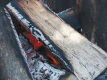Die hölzernen Klotz brennen im Lagerfeuer, bevor sie ein Lebensmittel auf a kochen Lizenzfreies Stockfoto