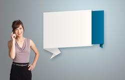 Die hübsche Frau, die nahe bei modernem Origami steht, kopieren Raum und maki Lizenzfreies Stockbild