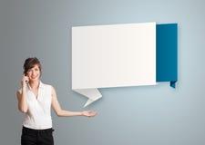 Die hübsche Frau, die nahe bei modernem Origami steht, kopieren Raum und maki Lizenzfreies Stockfoto