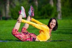 Die hübsche Frau, die Yoga tut, trainiert im Park Lizenzfreies Stockfoto