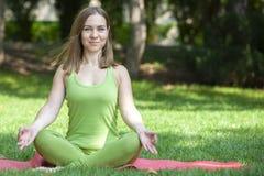 Die hübsche Frau, die Yoga tut, trainiert im Park lizenzfreies stockbild