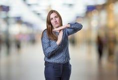 Die hübsche Geschäftsfrau, die Zeit heraus macht, gestikulieren über Unschärfe backgrou Lizenzfreie Stockfotografie