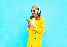 Die hübsche lächelnde Frau der Mode, die Smartphone verwendet, hört Musik stockfoto