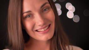 Die hübsche lachende Frau und passt neugierig in Kamera auf Bluredlichthintergrund auf stock video