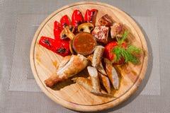 Die Hühnerschenkel, die mit Tomaten, Dill, Paprika gegrillt wurden, dienten mit Würsten und Pilzen auf hölzerner Platte stockfotografie