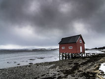 Die Hütte des roten Fischers nahe dem Meer in Tromso an einem bewölkten Tag Stockfotos