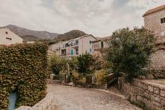 Die h?gelige Stra?e mit kleinen G?rten, die H?uschen und die Hotels umgebend, Budva Montenegro lizenzfreies stockfoto