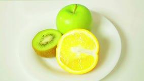 Die H?lften der orange Kiwi und des gr?nen Apfels auf einer wei?en Platte in einen Kreis sich drehen stock video