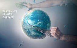 Die H?nde der M?nner rei?en eine Plastiktasche von der Kugel von Planet Erde auseinander Das Konzept des Umweltschutzes eco T?nun stockbilder
