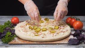 Die H?nde des Chefs in den Silikonhandschuhen, die ein St?ck Essiggurken zu seiner k?stlichen frischen Pizza nehmen Feld Italieni lizenzfreie stockbilder