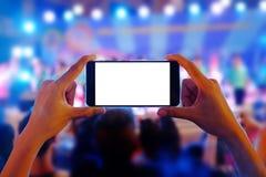 Die H?nde, die einen mobilen Smartphone halten, notiert buntes Livekonzert mit leerem wei?em Schirm stockfoto