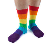 Die haarigen Beine der Männer in farbigem gestreiftem Sockenspaß isolat Stockbilder