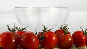 Die Hand bewegt die Tomaten in eine Schüssel stock footage