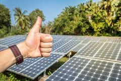 Die Hand, die Daumen oben durch den Hintergrund zeigt, ist Solarenergie Stockbild