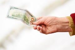 Die Hand der älteren Frau geben weg Geld lizenzfreies stockbild