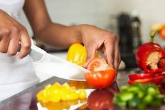Die Hand der Afroamerikanerfrau, die ein tomatoe schneidet stockfotografie