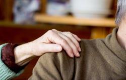 Die Hand der Frau auf der Schulter des Mannes lizenzfreies stockbild