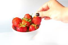 Die Hand der Frau, die eine frische Erdbeere aufhebt Stockbild