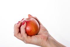 Die Hand der Frau, die einen roten Apfel auf Weiß erfasst Lizenzfreie Stockbilder