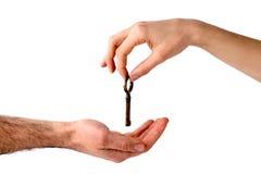 Die Hand der Frau, die einen Schlüssel zu einer Hand der Männer gibt Stockfotografie