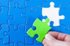 Die Hand der Frau, die fehlendes Stück beim Puzzlebedeuten legt Stockfotos