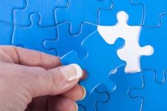 Die Hand der Frau, die fehlendes Stück beim Puzzlebedeuten legt Lizenzfreies Stockbild