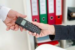 Die Hand der Frau, die ihrem Kollegen ein Telefon gibt stockbild