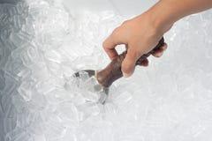 Die Hand der Frau, die Löffel auf Eis hält Lizenzfreie Stockbilder