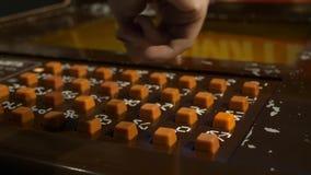 Die Hand der Frau drückt orange Knöpfe auf brauner Platte des Spielautomaten stock video footage