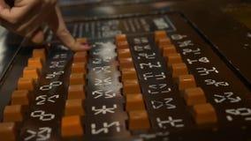Die Hand der Frau drückte orange Knöpfe auf brauner Platte des Spielautomaten stock video footage