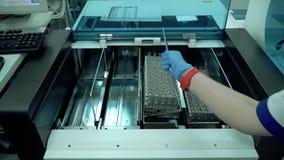 Die Hand der Frau, die Gestelle mit Reagenzgläsern in den Maschinenabschluß oben einsetzt Elektronische Ausrüstung im Labor Masch stock video