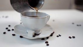 Die Hand der Frau gießt Kaffee von einem Topf des türkischen Kaffees in eine weiße Schale auf einer weißen Tabelle Zimt und Kaffe stock video
